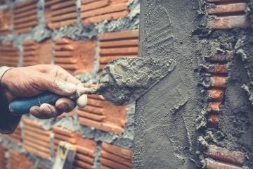foto van een muur in opbouw met truweel
