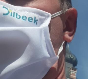 man met mondmasker met logo Dilbeek