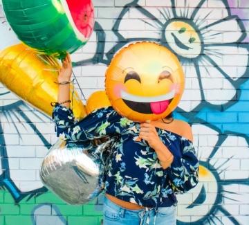 foto van een vrouw met een ballon van een gekke emoticon voor haar hoofd