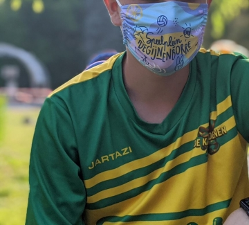 foto jongen met mondmasker met opschrift 'speelplein Begijnenborre'