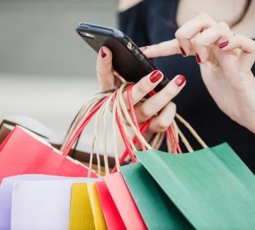 vrouw met winkeltassen en smartphone