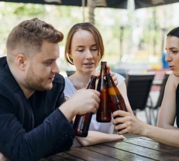 drie mensen klinken op een terras