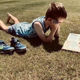 nabootsing schilderij jongen lezend liggend in het gras