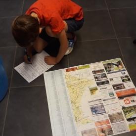 jongen klasvloer kaartlezen vult blad in